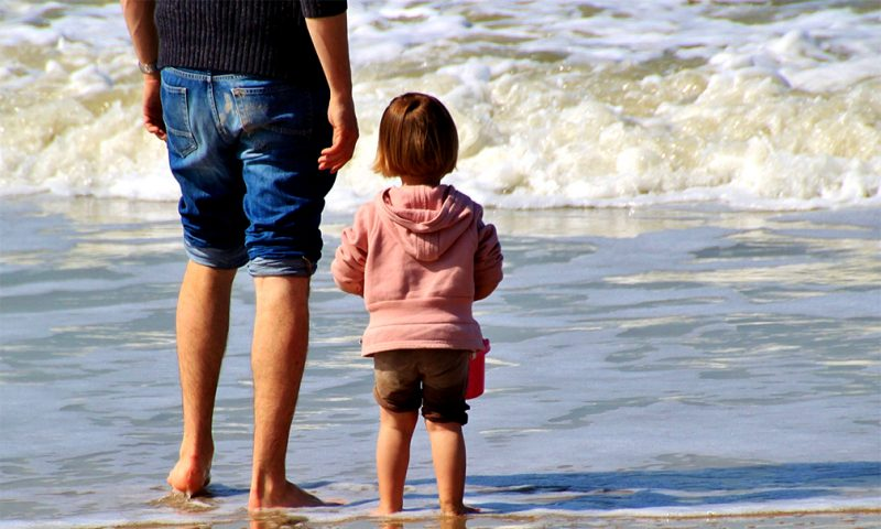 Step father and child get to know each other on the beach